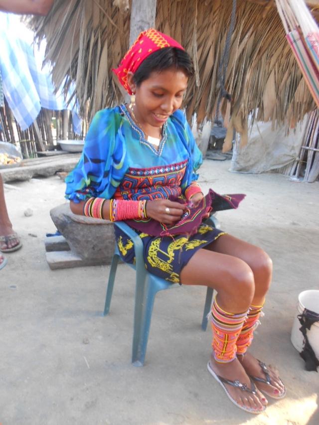 Een jonge dame in kunadracht: veel kralen, een mola om het bovenlichaam met mouwen en als rok een geknoopte lap.