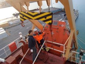 Inspecteur Lutz bij de valboot, een reddingsboot die schuin naar beneden valt als iedereen aan boord zit. In dit geval was het loslaat-mechaniek vast geschilderd.
